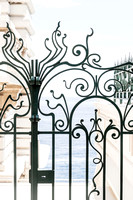 Ornate iron gate with the Mediterranean in the background | Cattie Coyle Photography